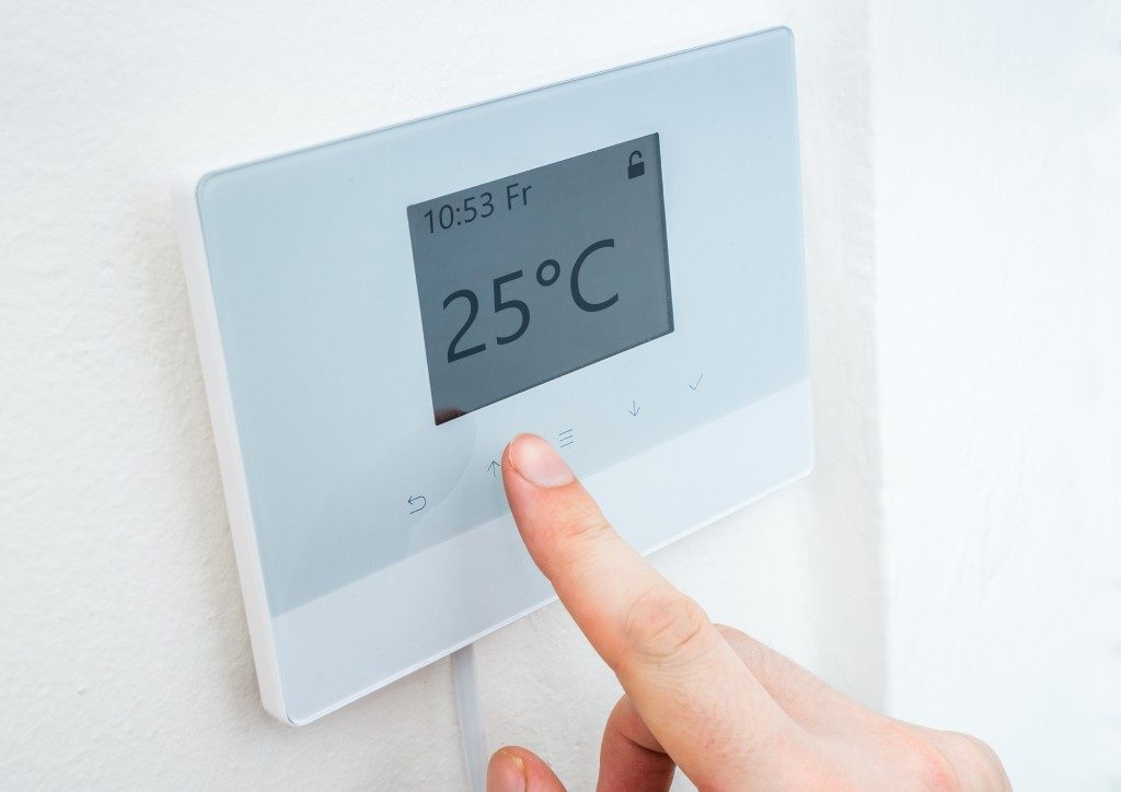 Hand adjusting temperature in the room