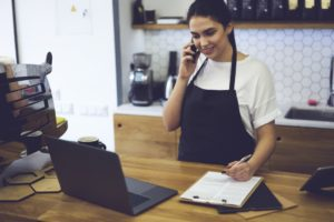 Businesswoman talking on the phone while looking at the laptop