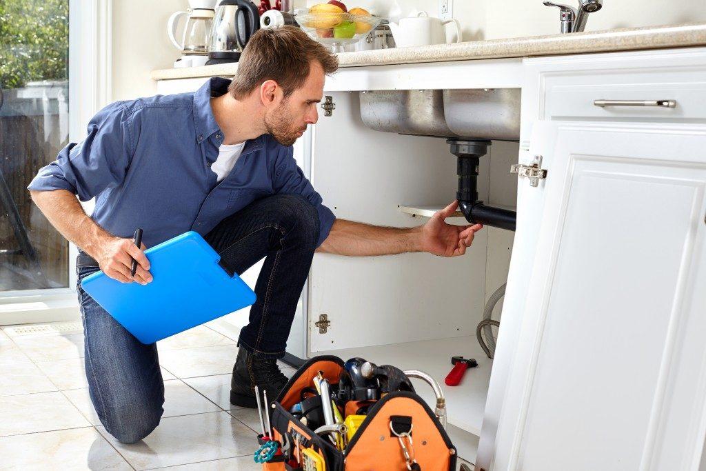 plumber fixing faucet pipe