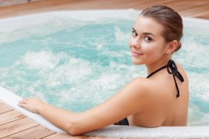 woman enjoying jacuzzi in spa center