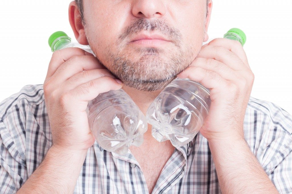 Man cooling his neck using cold water plastic bottles.