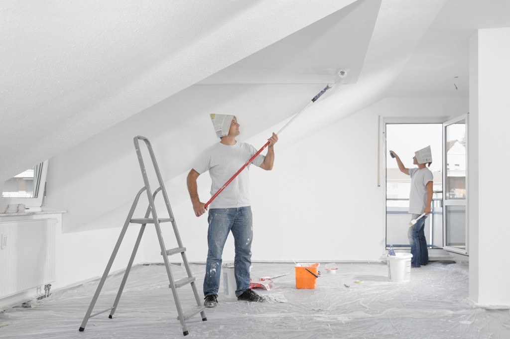 construction workers painting the ceiling