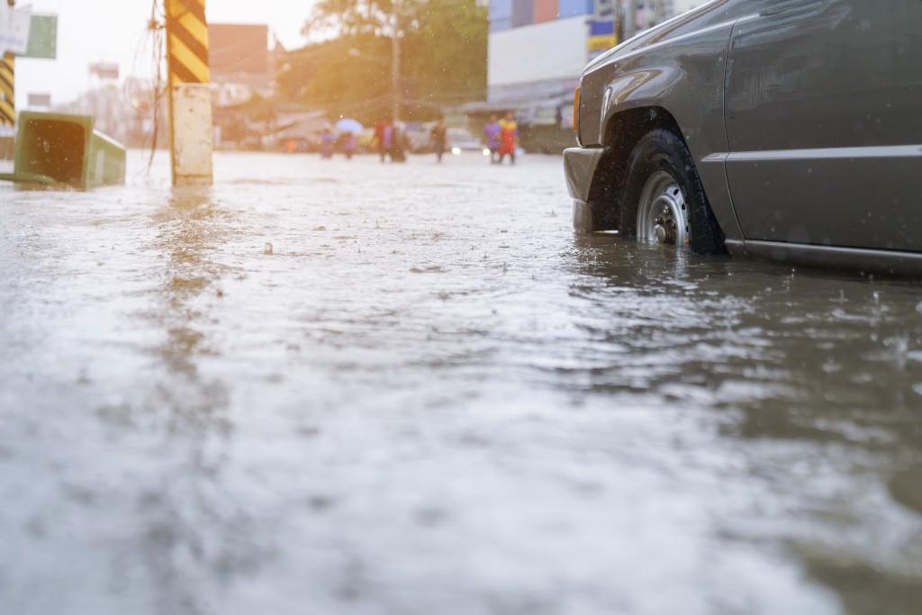 flood water - people walking in the rain on flooded road