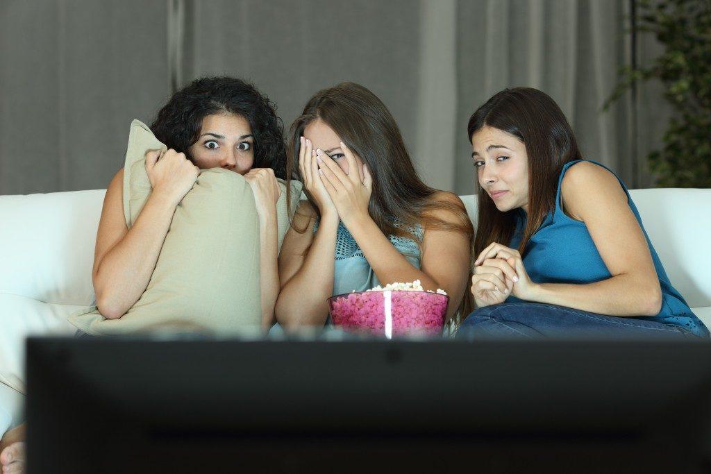 Girls watching a terror movie on tv