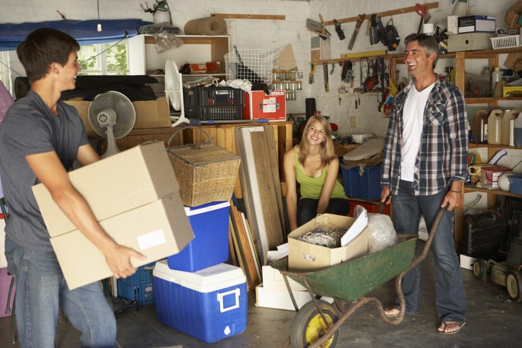 teenagers and father cleaning garage