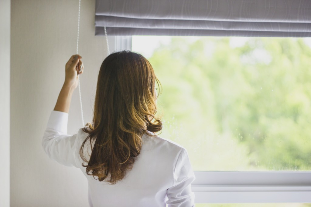 woman opening blinds of her window