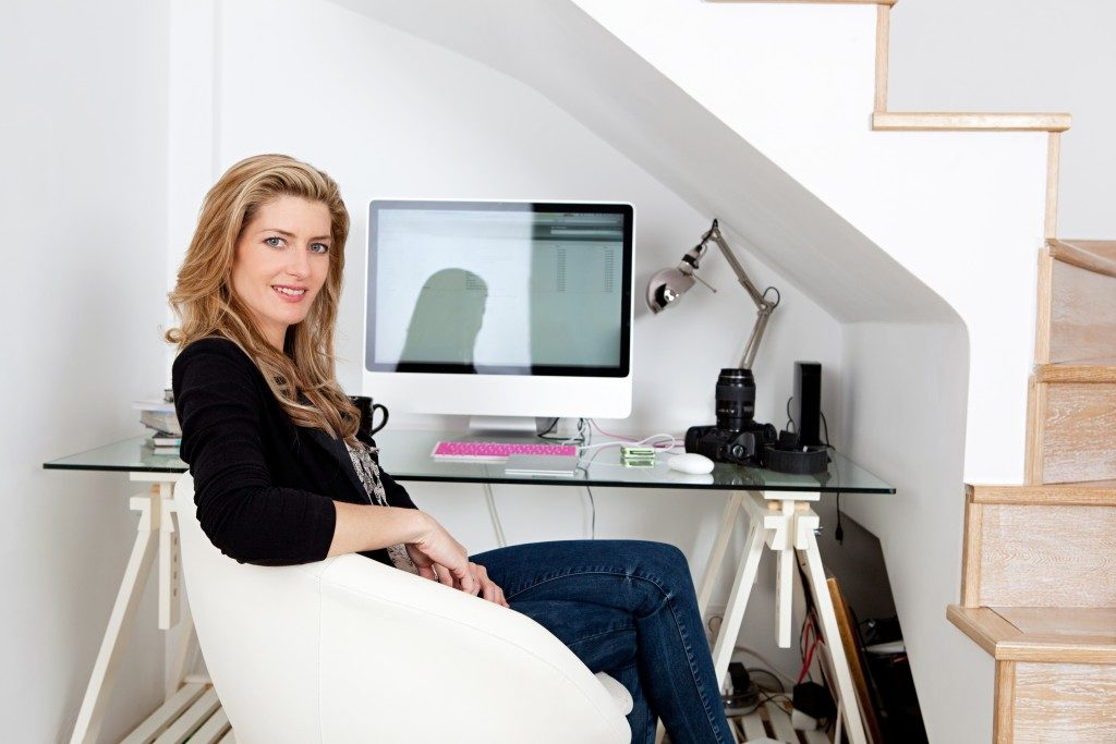 professional photographer working from home and sitting at her desk at home, with her camera equipment