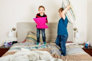 toddlers jumping on the bed