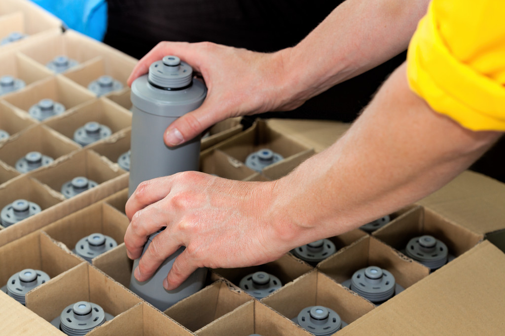 Grey bottles being packed in factory