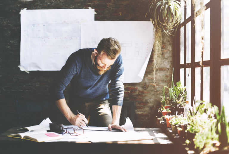 man drafting a blueprint